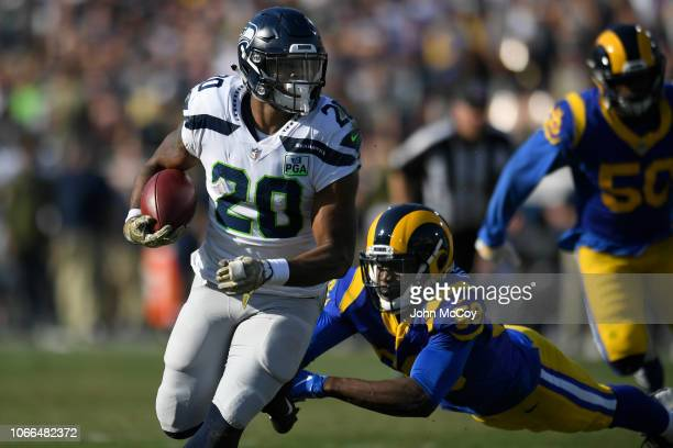 Rashaad Penny of the Seattle Seahawks runs away from Cory Littleton of the Los Angeles Rams at Los Angeles Memorial Coliseum on November 11 2018 in...
