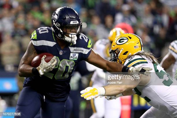 Rashaad Penny of the Seattle Seahawks runs with the ball in the first quarter against Clay Matthews of the Green Bay Packers during their game at...