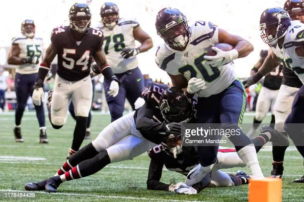 Rashaad Penny of the Seattle Seahawks runs with the ball under pressure from defender Damontae Kazee of the Atlanta Falcons during the second quarter...