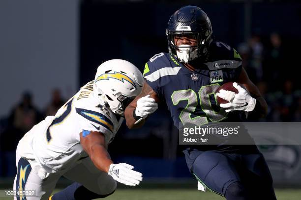 Rashaad Penny of the Seattle Seahawks runs with the ball while being chased by Uchenna Nwosu of the Los Angeles Chargers in the first quarter at...