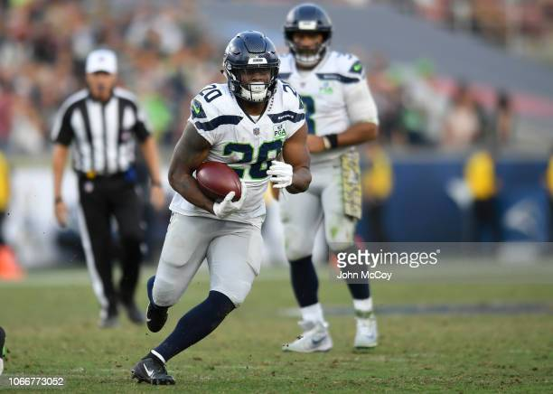 Rashaad Penny of the Seattle Seahawks rushes against the Los Angeles Rams at Los Angeles Memorial Coliseum on November 11 2018 in Los Angeles...