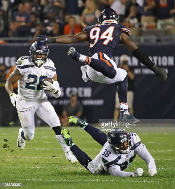 Rashaad Penny of the Seattle Seahawks rushes as Tevon Mutcherson knocks Leonard Floyd of the Chicago Bears into the air at Soldier Field on September...