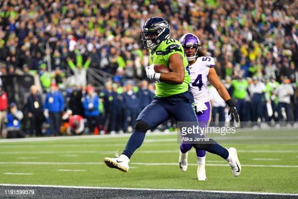 Rashaad Penny of the Seattle Seahawks scores a touchdown after a 13 yard pass from Russell Wilson during the fourth quarter of the game against the...