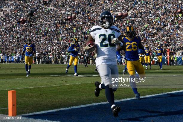 Rashaad Penny of the Seattle Seahawks scores a touchdown being followed by Mark Barron of the Los Angeles Rams at Los Angeles Memorial Coliseum on...