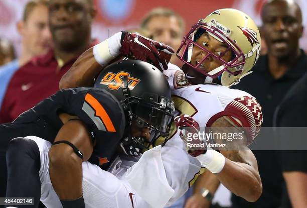Rashad Greene of the Florida State Seminoles makes the catch as Kevin Peterson of the Oklahoma State Cowboys defends in the first half of the...