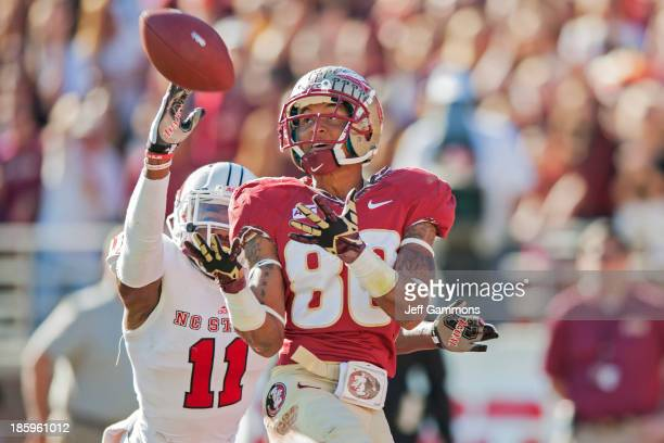 Rashad Greene of the Florida State Seminoles reels in a touchdown pass while Juston Burris of the North Carolina State Wolfpack attempts to defend...