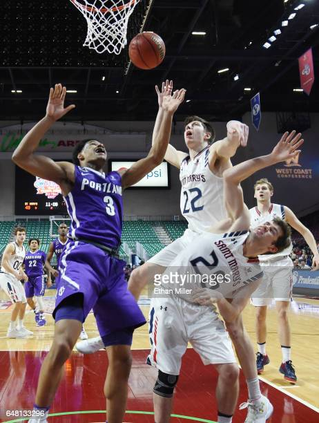 Rashad Jackson of the Portland Pilots goes after a rebound against Dane Pineau and Joe Rahon of the Saint Mary's Gaels during a quarterfinal game of...