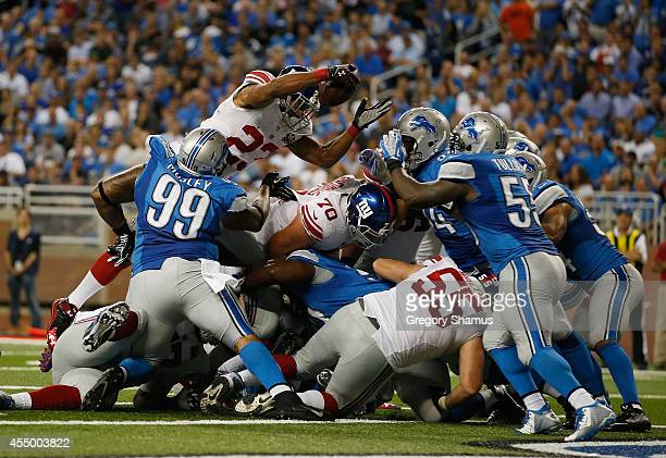 Rashad Jennings of the New York Giants dives for a fourth quarter touchdown between C.J. Mosley and Stephen Tulloch of the Detroit Lions at Ford...