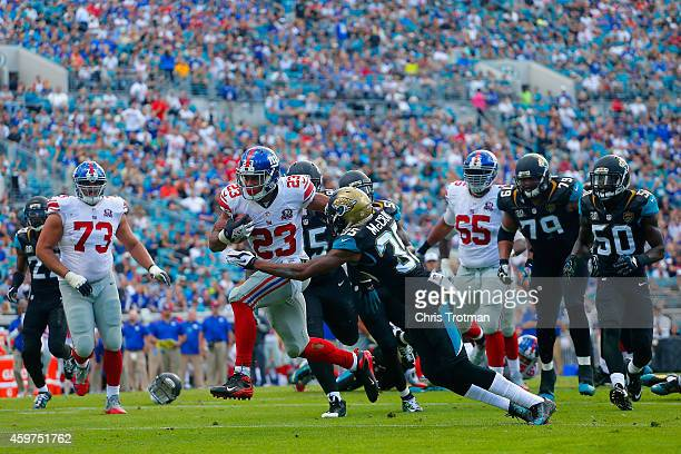 Rashad Jennings of the New York Giants is challenged by Demetrius McCray of the Jacksonville Jaguars as he runs the ball back for a touchdown in the...