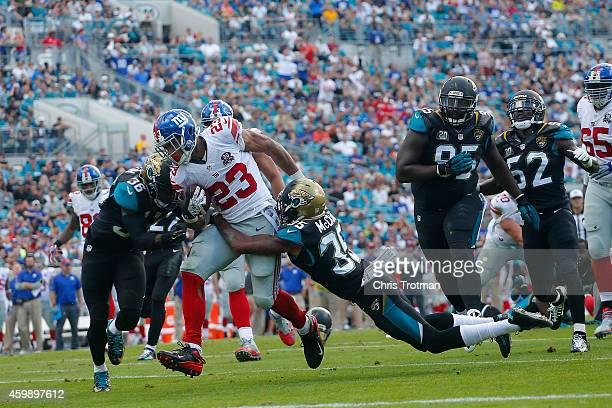 Rashad Jennings of the New York Giants is tackled by Demetrius McCray of the Jacksonville Jaguars at EverBank Field on November 30 2014 in...