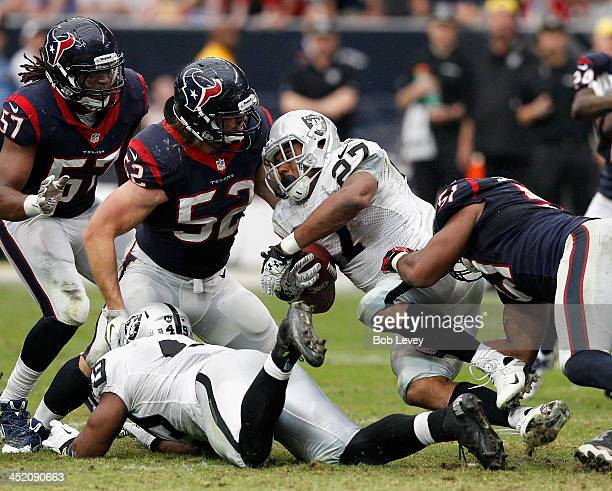 Rashad Jennings of the Oakland Raiders is tackled by Darryl Sharpton of the Houston Texans and Jeff Tarpinian at Reliant Stadium on November 17 2013...