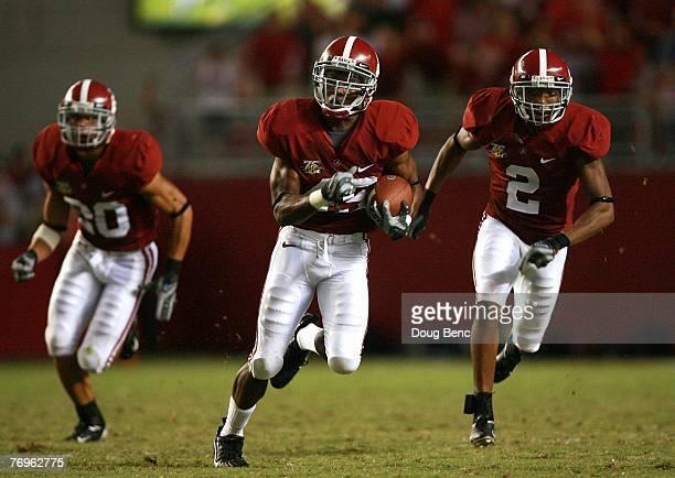 Rashad Johnson of the Alabama Crimson Tide flanked by teammates Marcus Carter and Simeon Castille returns an interception against the Georgia...