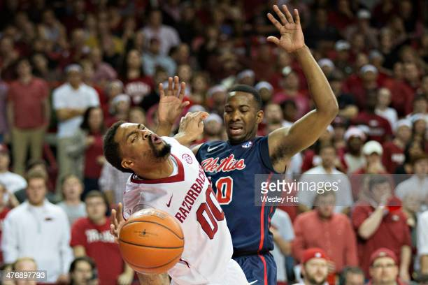 Rashad Madden of the Arkansas Razorbacks is fouled by LaDarius White of the Ole Miss Rebels at Bud Walton Arena on March 5, 2014 in Fayetteville,...