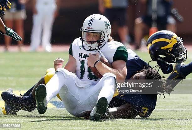 Rashan Gary of the Michigan Wolverines loses his helmet while tackling Dru Brown of the Hawaii Warriors during the third quarter on September 3 2016...