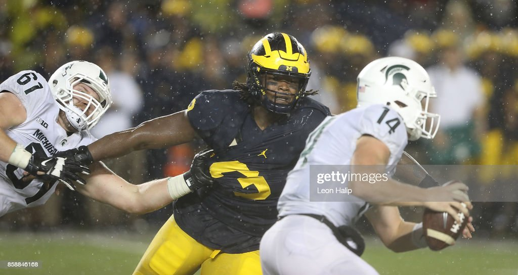 Rashan Gary #3 of the Michigan Wolverines makes the stop on Brian Lewerke #14 of the Michigan State Spartans during the fourth quarter of the game at Michigan Stadium on October 7, 2017 in Ann Arbor, Michigan. Michigan State defeated Michigan 14-10.