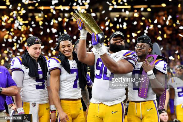 Rashard Lawrence of the LSU Tigers raises the National Championship Trophy with Joe Burrow Grant Delpit Patrick Queen and Rashard Lawrence after the...