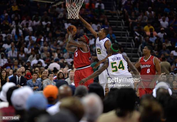 Rashard Lewis of 3 Headed Monsters defends a shot by Al Harrington of Trilogy during week two of the BIG3 three on three basketball league at...
