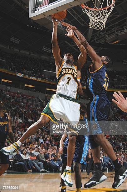 Rashard Lewis of the Seattle SuperSonics goes to the basket against the defense of Nene of the Denver Nuggets on APRIL 1 2007 at the Key Arena in...