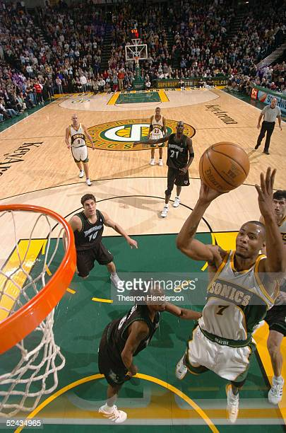 Rashard Lewis of the Seattle SuperSonics shoots against the Minnesota Timberwolves Wally Szczerbiak and Troy Hudson on February 25 2005 at Key Arena...