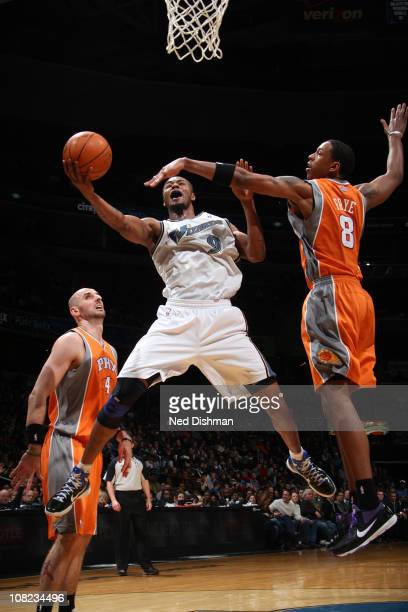 Rashard Lewis of the Washington Wizards shoots against Channing Frye and Marcin Gortat of the Phoenix Suns at the Verizon Center on January 21 2011...