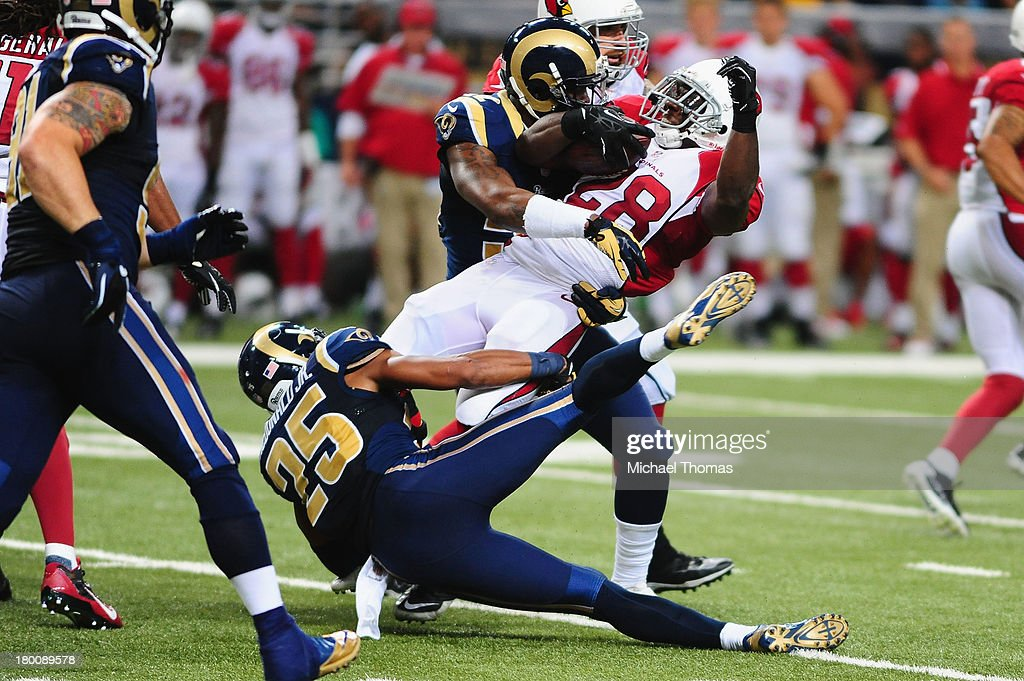 Rashard Mendenhall #28 of the Arizona Cardinals is tackled by T.J. McDonald and Alec Ogletree both of the St. Louis Rams at the Edward Jones Dome on September 8, 2013 in St. Louis, Missouri.