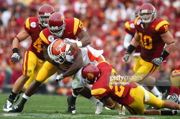"""Rashard Mendenhall of the Illinois Fighting Illini is tackled by Keith Rivers and Terrell Thomas of the USC Trojans during the """"Rose Bowl presented..."""