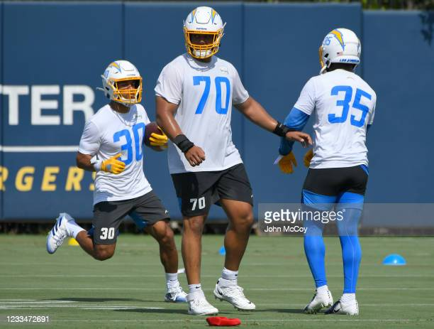 Rashawn Slater blocks for Austin Ekeler while Larry Rountree III of the Los Angels Chargers rushes during mandatory minicamp on June 15, 2021 in...