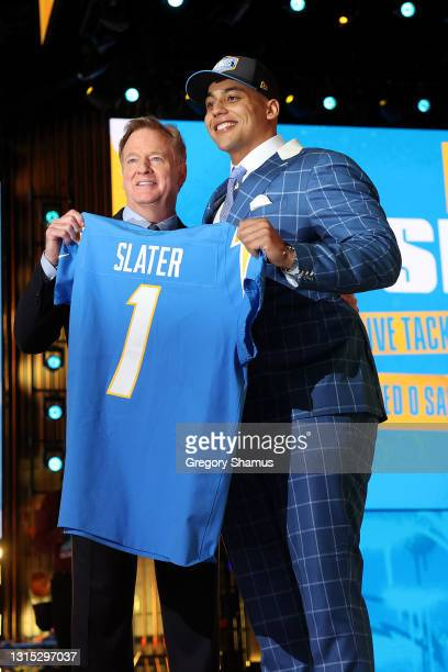 Rashawn Slater poses with NFL Commissioner Roger Goodell onstage after being selected 13th by the Los Angeles Chargers during round one of the 2021...
