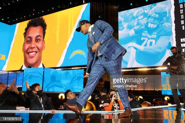 Rashawn Slater walks onstage after being selected 13th by the Los Angeles Chargers during round one of the 2021 NFL Draft at the Great Lakes Science...