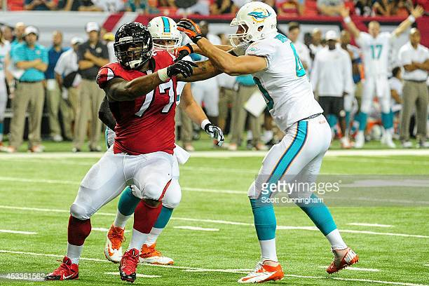 Ra'Shede Hageman of the Atlanta Falcons pushes past Brett Brackett of the Miami Dolphins in the fourth quarter of a preseason game at the Georgia...