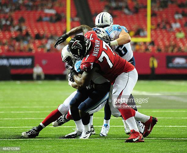 Ra'Shede Hageman of the Atlanta Falcons tackles Bishop Sankey of the Tennessee Titans in a preseason game at the Georgia Dome on August 23 2014 in...