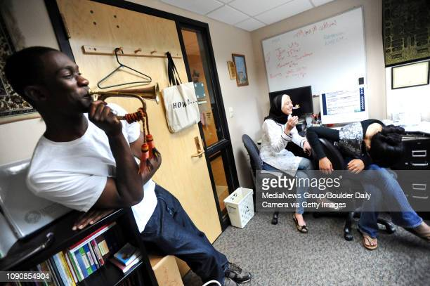 Rasheed Lawal left a University of Colorado student who is a member of the Muslim Students Association blows a horn that hangs in the student office...
