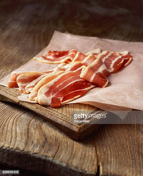 Rashers of raw streaky bacon on baking paper