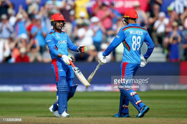 Rashid Khan and Mujeeb Ur Rahman of Afghanistan celebrate their 200 during the Group Stage match of the ICC Cricket World Cup 2019 between...