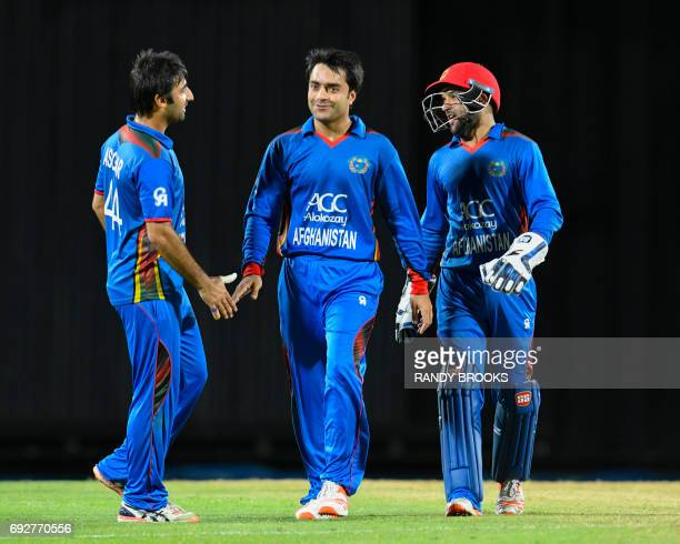 Rashid Khan Mohamad Asghar Stanikzai and Shafiqullah Shafaq of Afghanistan celebrate the dismissal Lendl Simmons of West Indies during the 3rd and...