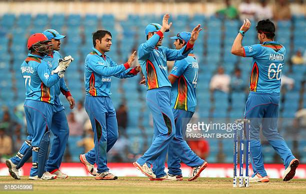 Rashid Khan of Afganistan celebrates the wicket of Vusi Sibanda of Zimbabwe with teammates during the T20 World Cup cricket match between Zimbabwe...