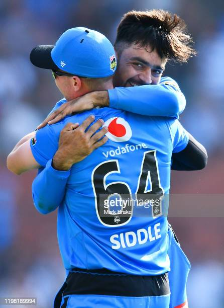 Rashid Khan of the Strikers celebrates the wicket of Jordan Silk of the Sixers hugs Peter Siddle of the Strikers during the Big Bash League match...
