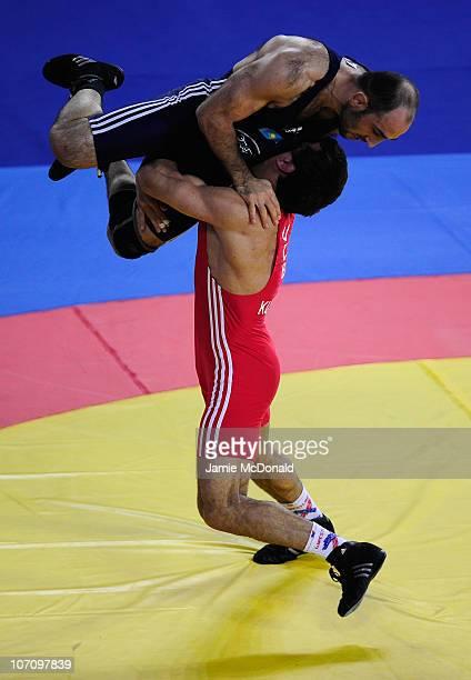 Rashid Kurbanov of Uzbekistan lifts Seifaddin Osmanov of Kazakhstan in the Men's Freestyle 74kg class at Huagong Gymnasium during day twelve of the...