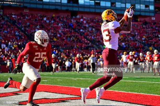 Rashod Bateman of the Minnesota Golden Gophers scores a touchdown as Jarrett Paul of the Rutgers Scarlet Knights looks on during the second quarter...