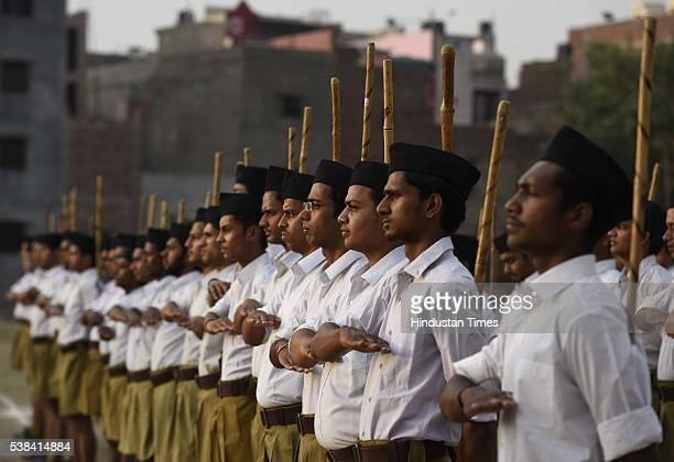 Rashtriya Swayamsevak Sangh volunteers hold sticks as they pray during a RSS Volunteer Training Camp at Gandhi Nagar on June 6 2016 in New Delhi...