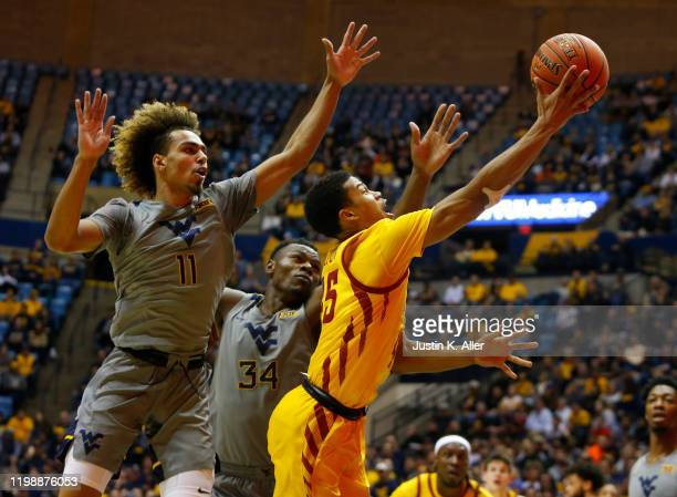 Rasir Bolton of the Iowa State Cyclones drives to the rim against Emmitt Matthews Jr #11 of the West Virginia Mountaineers at the WVU Coliseum on...