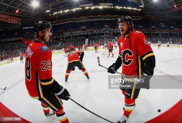 Rasmus Andersson and Elias Lindholm of the Calgary Flames are all fired up before the game against the Arizona Coyotes at Scotiabank Saddledome on...