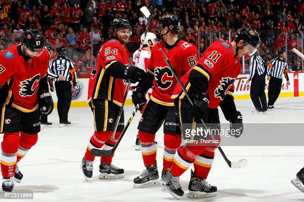 Rasmus Andersson Brett Kulak and teammates of the Calgary Flames celebrate a goal against the Detroit Red Wings during an NHL game on November 9 2017...
