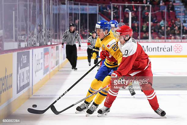 Rasmus Andersson of Team Denmark and Joel Eriksson Ek of Team Sweden chase the puck during the IIHF preliminary round game at the Bell Centre on...