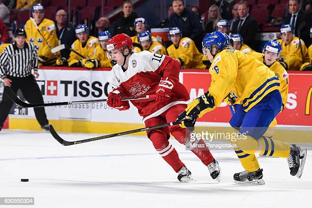 Rasmus Andersson of Team Denmark and Kristoffer Gunnarsson of Team Sweden skate for the puck during the IIHF preliminary round game at the Bell...