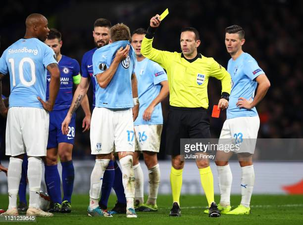 Rasmus Bengtsson of Malmo is shown his second yellow leading to a red card by referee Orel Grinfeld during the UEFA Europa League Round of 32 Second...