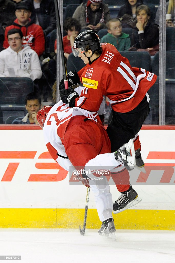Rasmus Bjerrum #25 of Team Denmark body checks Gaetan Haas #11 of Team Switzerland during a relegation game at the 2012 World Junior Hockey Championships at the Saddledome on January 2, 2012 in Calgary, Alberta, Canada.