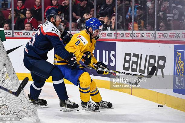 Rasmus Dahlin of Team Sweden and Miroslav Struska of Team Slovakia chase the puck into the boards during the 2017 IIHF World Junior Championship...