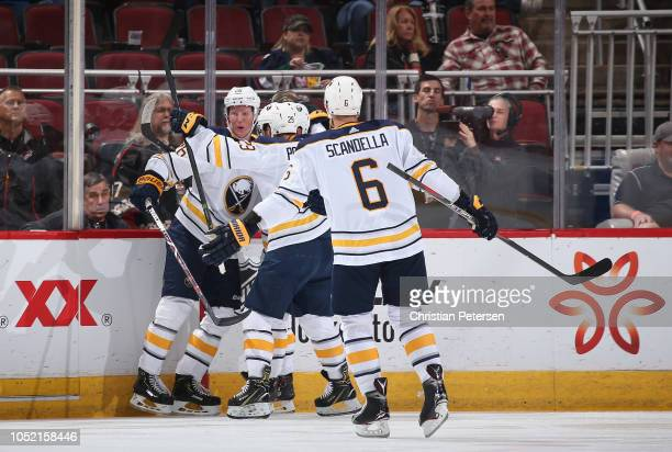Rasmus Dahlin of the Buffalo Sabres celebrates with Jason Pominville and Marco Scandella after scoring his first career goal against the Arizona...