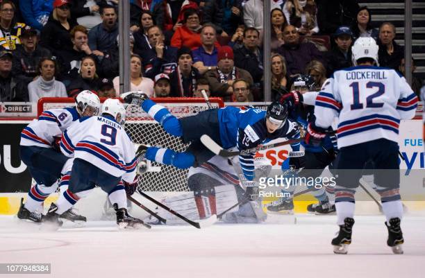 Rasmus Kupari of Finland goes flying through the crease and over goalie Cayden Primeau of the United States while trying to get a shot on net in Gold...